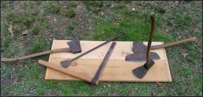From left to right, roughly: felling ax; barking spud; homemade froe (from a section of handrail and a strap hinge); broadax; and adz.
